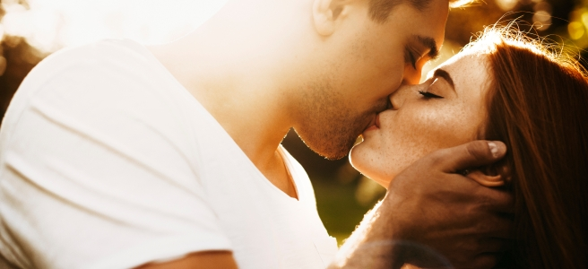 Man with facial hair kissing a red haired woman