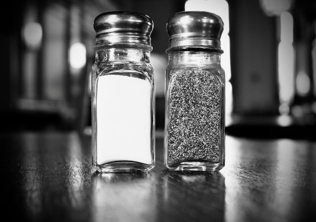 A black and white photo of salt and pepper shakers on a diner table, by Lachlan on Unsplash